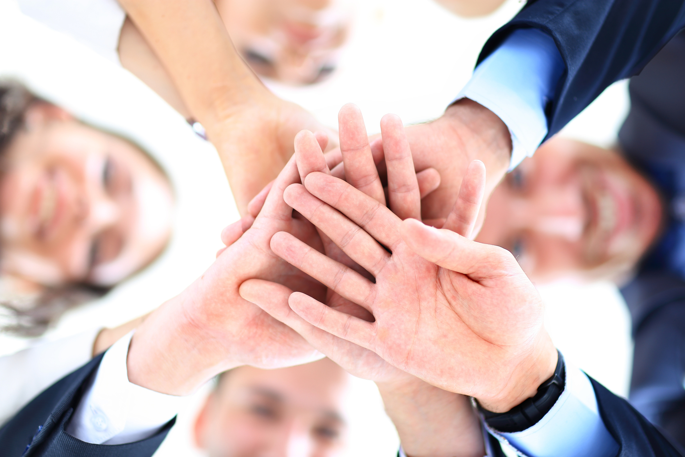 Small group of business people joining hands